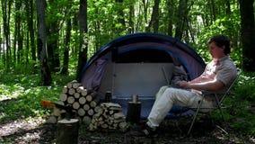 Mann, der draußen in einem Zeltlager arbeitet stock footage
