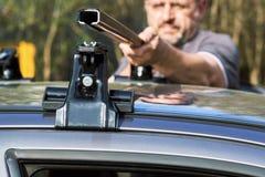 Mann, der draußen einen Autodachgepäckträger installiert lizenzfreies stockfoto