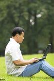 Mann, der draußen einen Laptop verwendet lizenzfreies stockbild