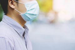 Mann, der draußen hygienische Maskenim gesichtnase trägt Ökologie, Luftverschmutzungsauto, Klima- und Virusschutz stockfotos