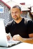 Mann, der draußen an Laptop arbeitet Stockfoto
