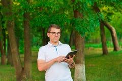 Mann, der draußen mit Tablet-Computer arbeitet Lizenzfreie Stockbilder
