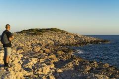Mann, der draußen am Steinstrandabschluß das adriatische Meer in Kroatien bei Sonnenuntergang steht Lizenzfreie Stockbilder