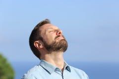 Mann, der draußen tiefe Frischluft atmet Lizenzfreies Stockbild