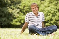 Mann, der draußen lächeln sitzt Lizenzfreie Stockfotos