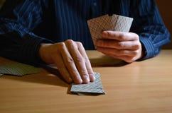 Mann in der Dunkelheit, die einen Satz Spielkarten und eine von ihnen, strategisches Wettbewerbskonzept des Geschäfts nehmen hält lizenzfreie stockbilder