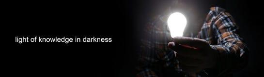 Mann in der Dunkelheit mit Glühenbirne Lizenzfreie Stockfotos