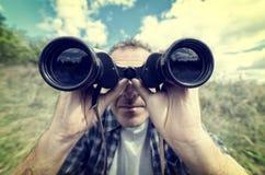 Mann, der durch binokulares schaut stockfotos