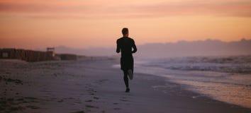 Mann, der durch das Meer am Morgen läuft lizenzfreie stockfotos