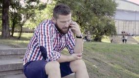 Mann 20_057, der durch den Smartphone, sitzend auf Treppe spricht Schieber- und Wannenschuß Bewegungen stock video footage