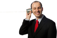 Mann, der durch ein Dosentelefon und -c$lachen hört Lizenzfreies Stockbild