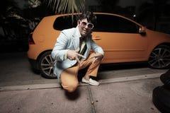 Mann, der durch ein Orangensportauto aufwirft Lizenzfreie Stockfotos