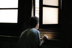 Mann, der durch Fenster schaut Stockfotos