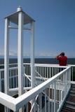 Mann, der durch Ferngläser an der Spitze des Hafen-Lichtes schaut Stockfotografie