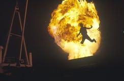 Mann, der durch Feuerkugel springt stockbild