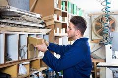 Mann, der durch gespeicherte Einzelteile Werkstatt betrachtet Stockbilder