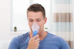 Mann, der durch Inhalator-Maske inhaliert Stockfotografie