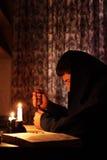 Mann, der durch Kerzenlicht sitzt stockbild