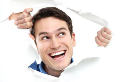 Mann, der durch Loch auf Papier lugt stockbild