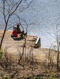 Mann, der durch See-Fischen für Forelle in Pandapas-Teich sitzt lizenzfreie stockfotografie