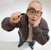 Mann, der durch Vergrößerungsglas blickt Lizenzfreie Stockfotos