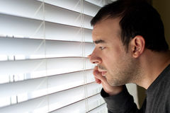 Mann, der durch Vorhänge späht Stockfotografie