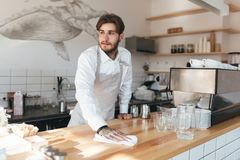 Mann, der durchdacht beiseite schaut und entgegengesetzt an seinem Arbeitsplatz im Restaurant abwischt stockfoto