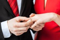 Mann, der Ehering auf Frauenhand setzt Stockfotografie