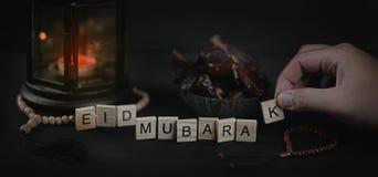 Mann, der Eid Mubarak Greeting Scrabble Letters vereinbart Ramadan Can Lizenzfreies Stockbild