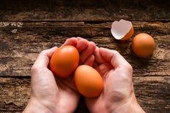 Mann, der Eier hölzern hält Lizenzfreies Stockbild