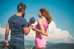 Mann der Eignung training Athletische Frau und starker bärtiger Mann, die Sitz mit Dummkopftraining hält Sexy Paare von Athleten lizenzfreie stockfotografie