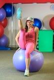 Mann der Eignung training Junges schönes weißes Mädchen in einer rosa Sportklage tut körperliche Bewegungen mit einem violetten S stockbild