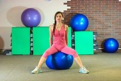 Mann der Eignung training Junges schönes weißes Mädchen in einer rosa Sportklage tut körperliche Bewegungen mit einem blauen Sitz lizenzfreies stockbild