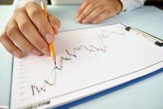 Mann, der ein aufwärts neigendes Diagramm analysiert Stockbilder