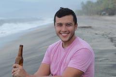 Mann, der ein Bier am Strand genießt stockfoto