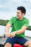 Mann, der ein Boot auf einem See rudert Stockfotografie