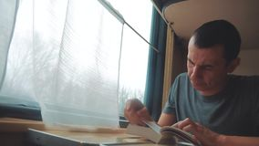 Mann, der ein Buch in einer langen Reise des Zugs liest Eisenbahnreisekonzepttrainer-Zugreise Ansicht sch?n vom Fenster stock footage
