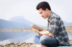 Mann, der ein Buch im Park auf einer Sommertagesflussseite liest stockbild