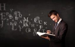Mann, der ein Buch mit Alphabetbuchstaben liest Lizenzfreie Stockbilder