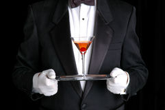 Mann, der ein Cocktail auf silbernem Tellersegment anhält Stockbilder