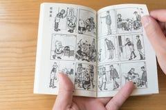 Mann, der ein Comic-Buch oben genannt Abschluss des alter Meister Q liest Lizenzfreie Stockfotografie
