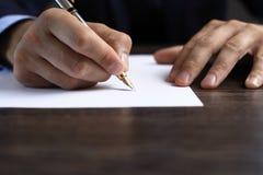 Mann, der ein Dokument unterzeichnet oder Korrespondenz schreibt stockfotos