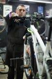 Mann, der ein Fahrrad repariert Stockfotografie