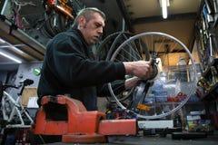 Mann, der ein Fahrrad repariert Stockbild