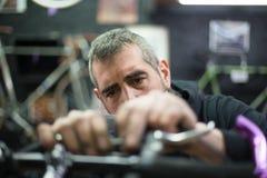 Mann, der ein Fahrrad repariert Lizenzfreie Stockfotos