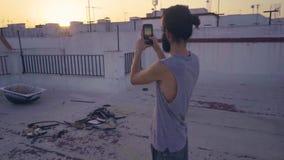 Mann, der ein Foto auf einer Dachspitze macht stock footage