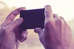 Mann, der ein Foto mit seinem Telefon macht Stockbild