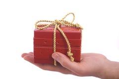 Mann, der ein Geschenk auf seiner Hand anbietet Lizenzfreie Stockfotos