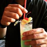 Mann, der ein Glas mit Cocktail hält lizenzfreies stockfoto