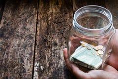 Mann, der ein Glasgefäß für Spendenkasten hält Stockfotos